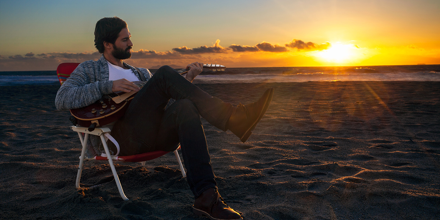 Guitarist playing a Line 6 Relay G10 guitar wireless on the beach into an AMPLIFi