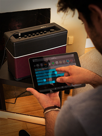 guitarist using Line 6 AMPLIFi Remote app on iOS and Android tablet