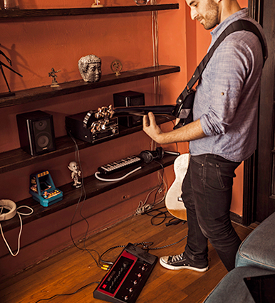 guitarist jamming on Line 6 FX100 guitar effects pedal at home