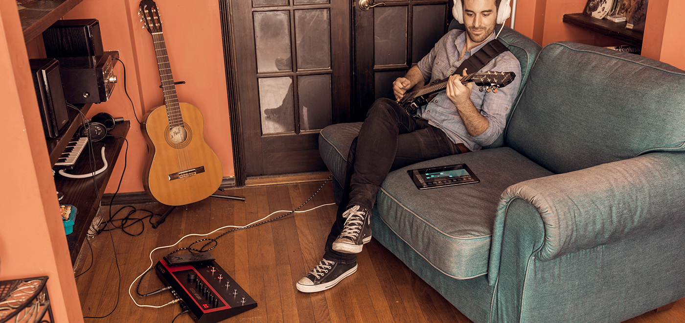 guitar player practicing on Line 6 FX100 guitar effects pedal with headphones and tablet